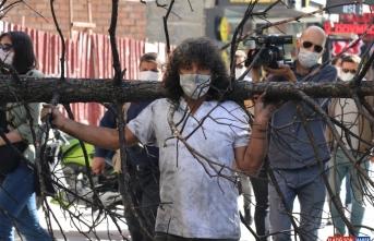 Orman yangınlarına yanmış ağacı omuzuna alıp caddede dolaşarak dikkati çekti